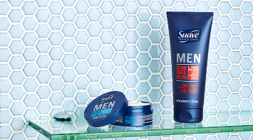 Container of Suave® Men Styling Paste and bottle of Suave® Men Styling Gel on a glass shelf in a tiled bathroom