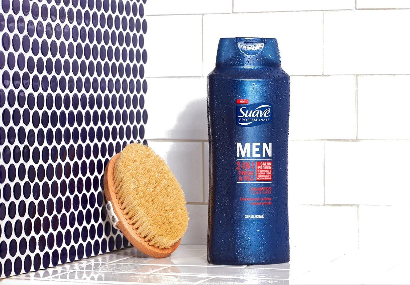 Bottle of Suave Men® 2-in-1 Thick & Full Shampoo and Conditioner in a shower next to a scrub brush