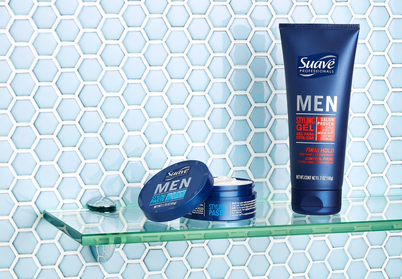 Container of Suave® Men Styling Paste and bottle of Suave Men® Styling Gel on a glass shelf in a tiled bathroom
