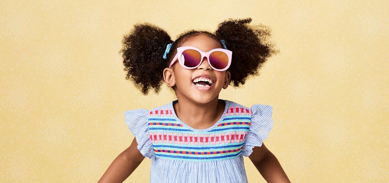 Girl wearing sunglasses and laughing with hair and skin cared for by Suave Kids®  Bath Products