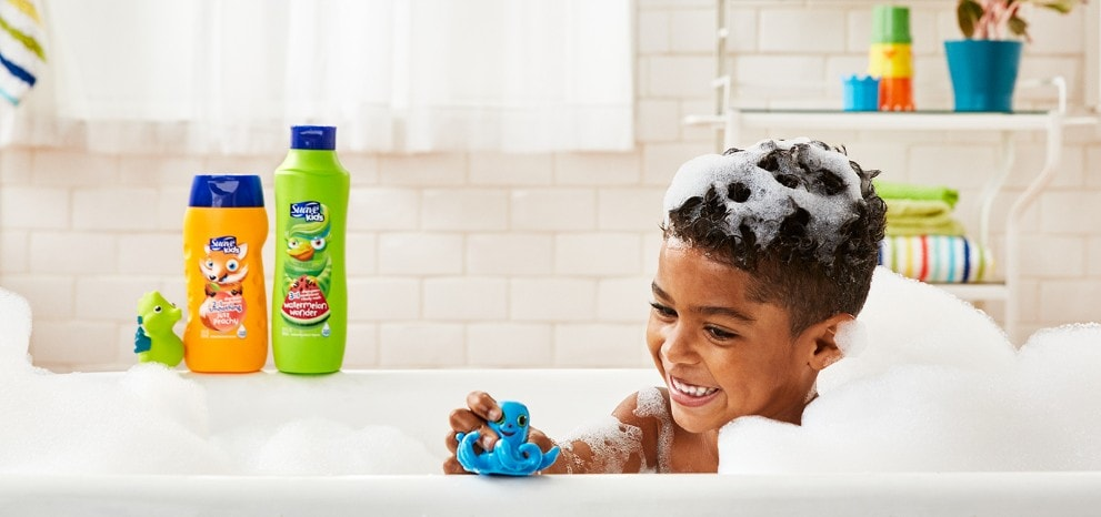 Boy playing with a toy in a bubble-bath and smiling with Suave® Kids® hair products