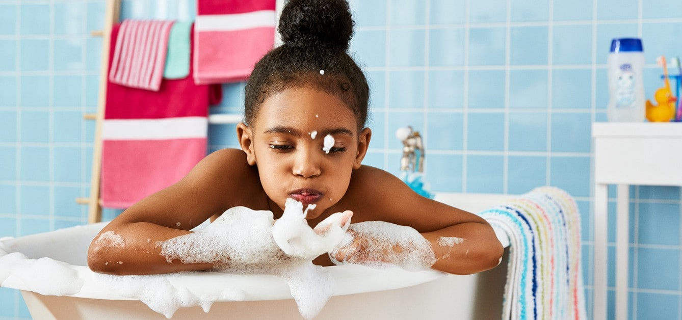 Girl playing with bubbles in a bathtub using Suave® Kids Body Wash
