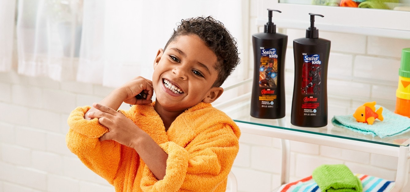 Boy in a bathroom smiling after using Suave Kids® Disney Collection