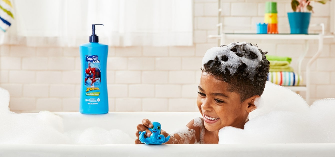Boy playing with a toy in a bubble-bath and smiling with Suave Kids® Marvel Spider-Man products