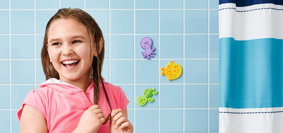Girl playing with bubbles in a bathtub using Suave Kids® Originals