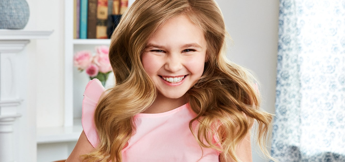 Girl smiling in her room with glowing hair cared for by Suave Kids®  Purely Fun
