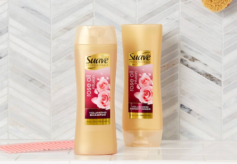 Botella de Suave® Rose Oil Infusion Volumizing Shampoo and Conditioner en un baño con azulejos junto a un peine