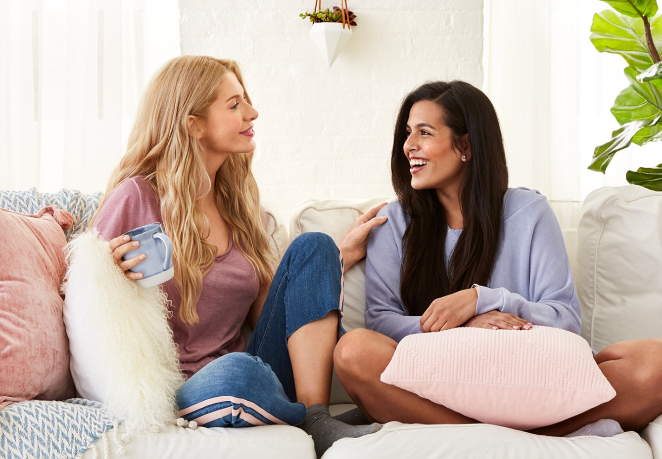 Two women chatting on a couch enjoying the results of Suave®
