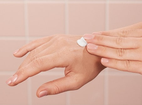 Applying Suave® Lotion to hands in a bathroom
