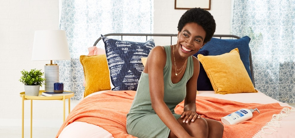 Woman sitting on the edge of a bed applying Suave® Body Care to her leg