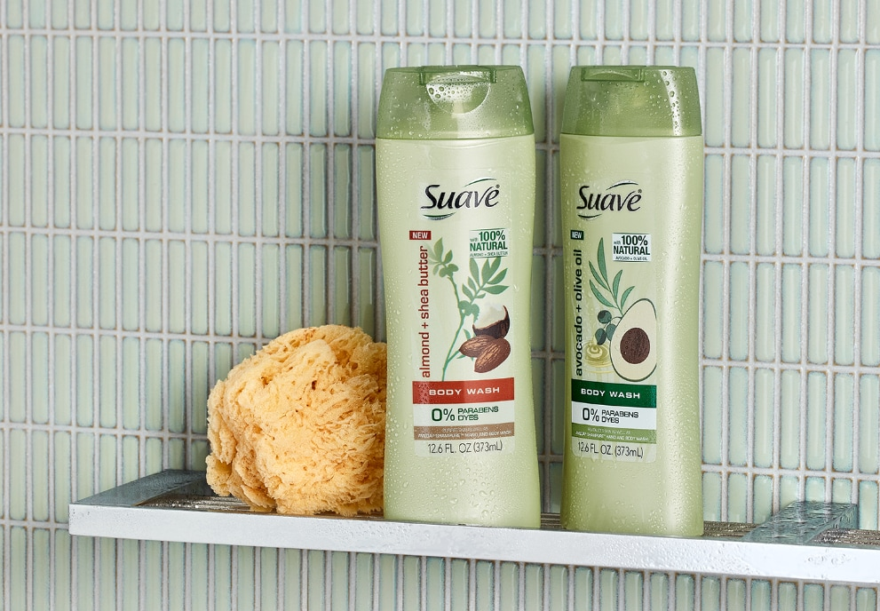 Two bottles of Suave® Creamy Body Wash in a shower next to a loofa