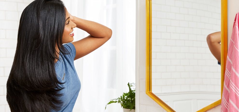 Woman looking in her bathroom mirror with healthy hair treated by Suave Professionals® Shampoo & Conditioner