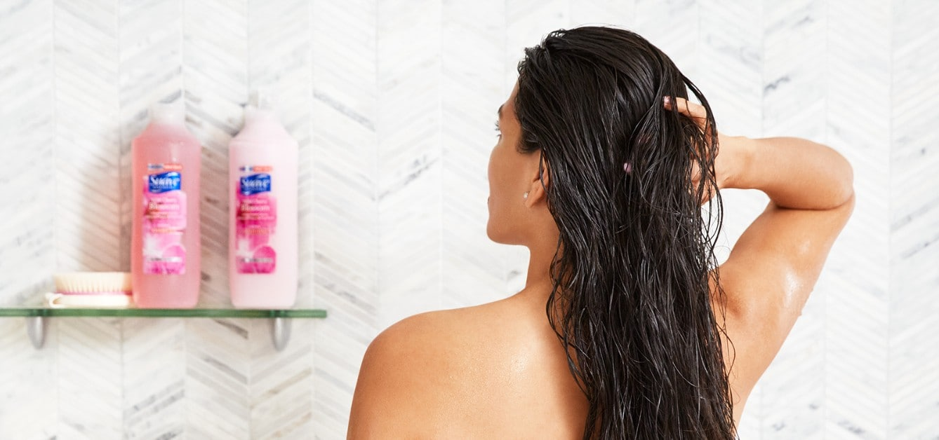Woman in a shower applying Suave Essentials® Shampoo & Conditioner