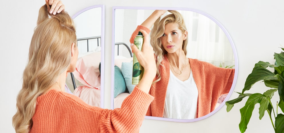 Woman getting ready in front of her bedroom mirror while applying Suave® Dry Shampoo & Styling