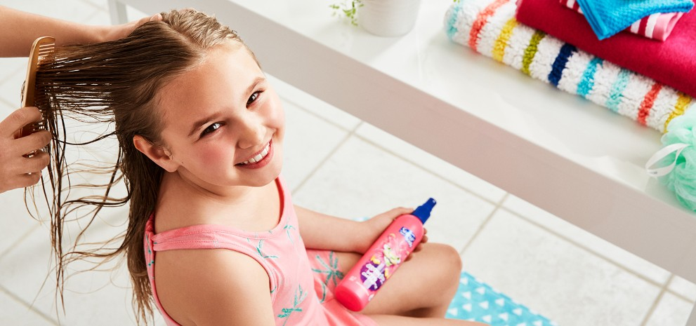 Girl smiling while her hair gets combed and detangled with Suave® Kids Detanglers & Styling products