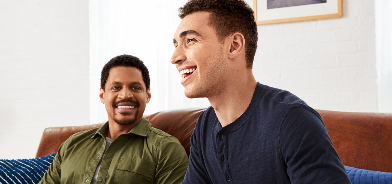 Two men smiling on a couch enjoying the results of Suave Men® Bath Products