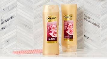 Bottle of Suave® Rose Oil Infusion Volumizing Shampoo and Conditioner in a tiled bathroom next to a comb