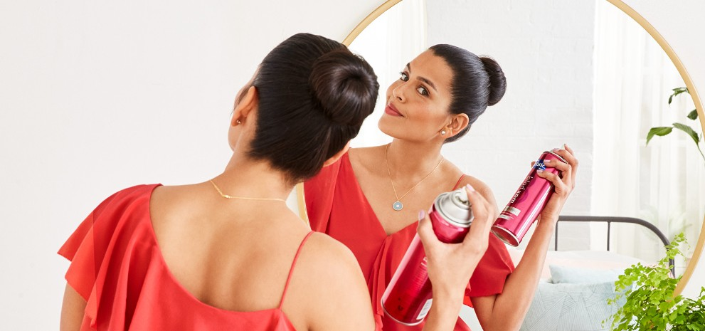 Woman looking in her bathroom mirror with healthy hair treated by Suave® Styling Collections