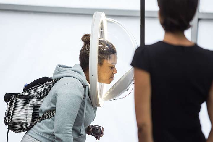 A woman leans her head into the bowl of a scent receptor to smell fragrance in an olfactory art exhibit, while the gallery employee looks on.