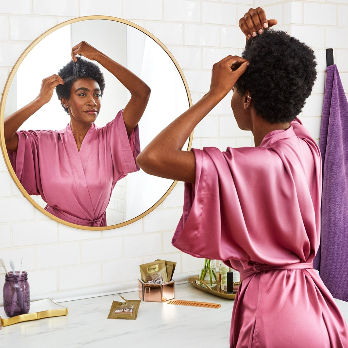 A woman looking in her bathroom mirror as she applies Suave Coconut Milk Infusion Moisture Mask