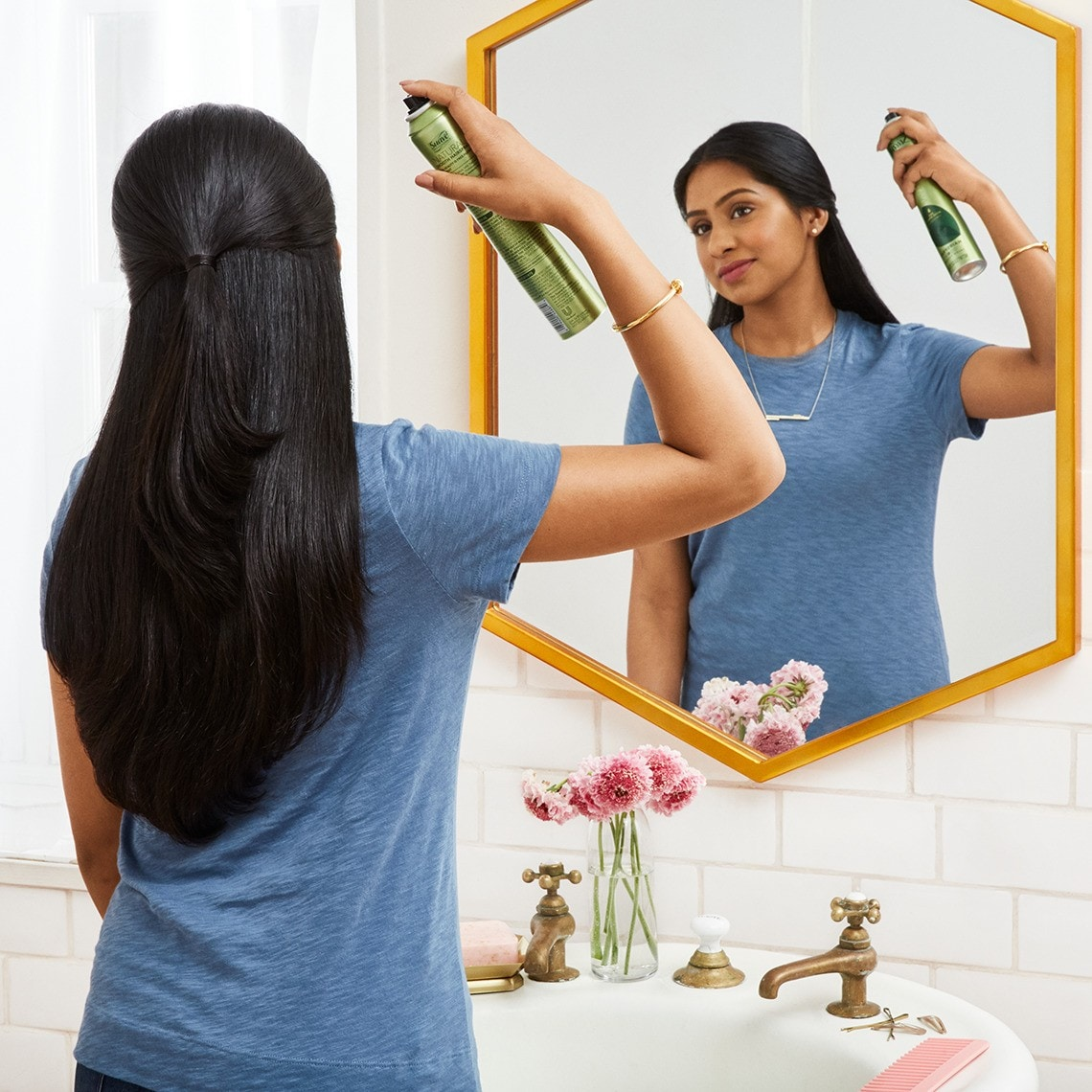 A woman looking in her bathroom mirror as she applies Natural Smooth Micro Mist Hairspray to her hair
