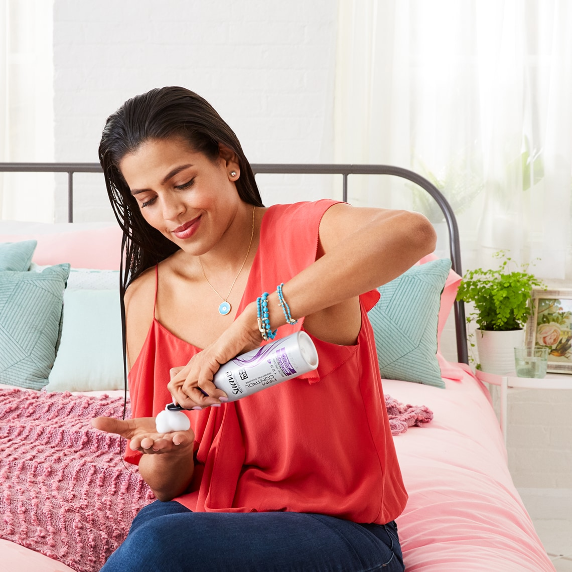 A woman with wet hair sitting on her bed. She is dispensing Suave Firm Control Mousse into her hand to apply to her hair.