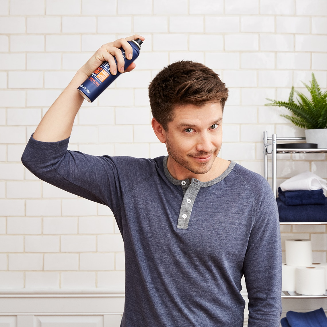 A man applies Suave Men's Hairspray to his hair while in his bathroom.