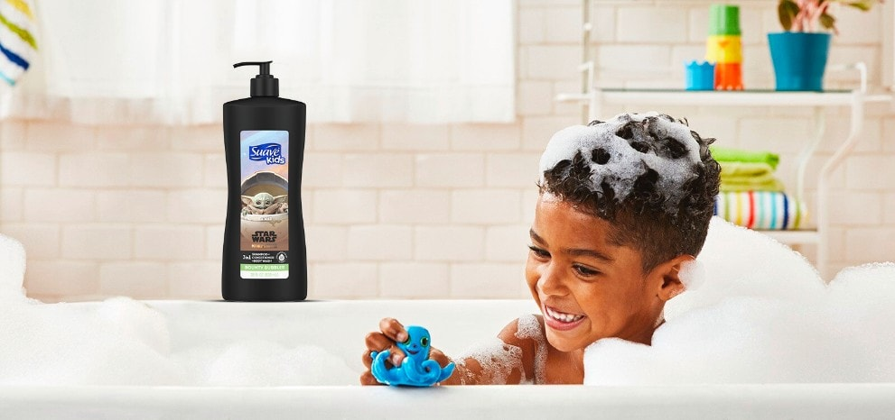 Boy playing with a toy in a bubble-bath and smiling with Suave Kids® Star Wars 3 in 1 Shampoo, Conditioner, Body Wash